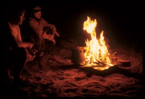 Patrons gather around the fire on the shore of the Salmon River